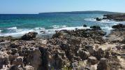Zona de rocas en la platja d'es Carnatge con vistas a La Mola