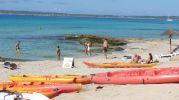 Varios kayak en primer plano y bañistas al fondo en playa Es Copinyar