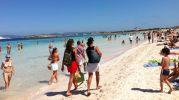 La playa llena de gente con agua cristalina