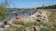 playa muy estrecha con sombrillas y hamacas