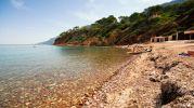 playa con muchisimas piedrecitas y rocas