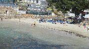 personas jugando en la playa y otras tomando el sol