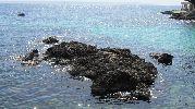 rocas en el mar  y un barco en mar abierto