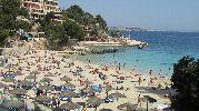 playa muy turística con sombrillas y hamacas