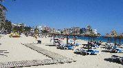 playa grande con sombrillas, hamacas y caminos de madera