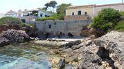 la playa esta limitada entre dos zona rocosas y un muro roto de piedra