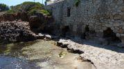 antiguo muro de piedra roto, al parecer, por las olas