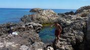 hombre manteniendo el equilibrio para pasar por las rocas