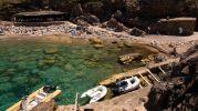 agua muy clara y grandes rocas en el fondo
