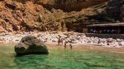 dos turistas entrando al agua y los demás tomando el sol