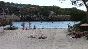 playa con hamacas, sombrillas y boyas para barcos en el agua