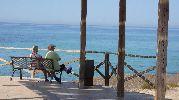 un banco con dos personas sentadas disdfrutando de paisaje a la sombra