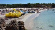 Vista de la zona de arena en Cala Saona, tumbonas  y sombrillas