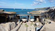 Casetas varadero, barcas y al fondo acantilados de La Mola