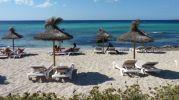 Cuatro sombrillas, bañistas y de fondo el agua azul y cristalina de la playa