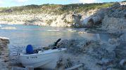 Barca en los varaderos y el acantilado de La Mola detrás