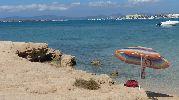 Sombrilla en primer plano, al fondo la isla de Ibiza