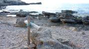Rocas y una cruz que recuerdan el nombre del lugar: Caló d'es Mort
