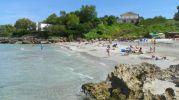 playa mediana con agua color azul grisáceo