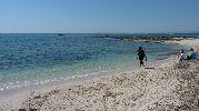 dos personas mirando el paisaje y una tercera cainando por la playa