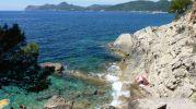 un turista tumbado en una roca tomando el sol