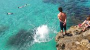 chicos saltando desde la roca al agua