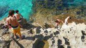 chicos saliendo del agua por las rocas