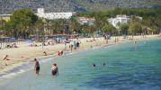 playa con sombrillas, hamacas y puesto de socorrismo