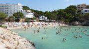 playa rodeada de hoteles y con bandera azul