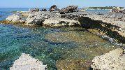 playa muy pequeña, rocosa y sin arena