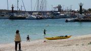 piragua en la arena  y de fondo el puerto